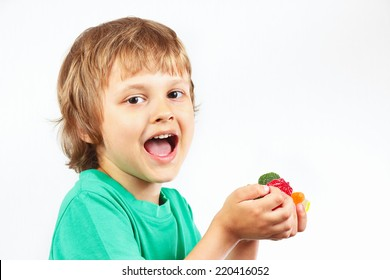 Little boy with colored sweets and jelly candies on a white background
