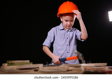 A little boy in a construction helmet is hammering nails in a locksmith's shop. The concept of child labor. Hobby in young age and help parents. Photo on a black background with copy space.