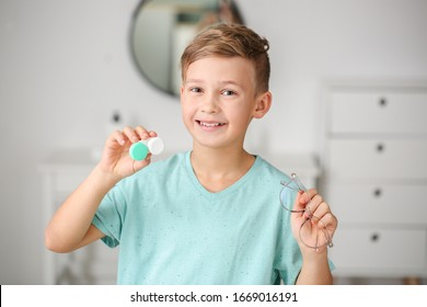 Little boy with contact lens case and eyeglasses at home