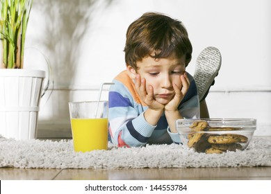 Little boy with cookies and orange juice stretching on carpet./ Child with diabetes looking cookies.