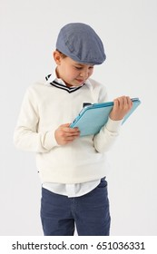 Little boy in cool hat using tablet pc.