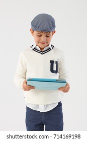 Little boy in cool hat using tablet computer.