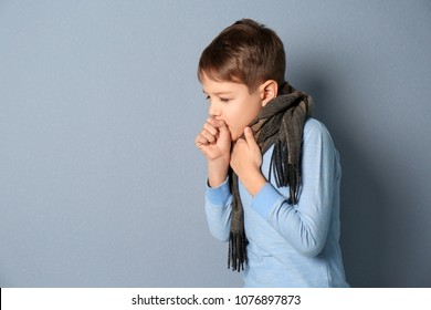 Little boy coughing on grey background