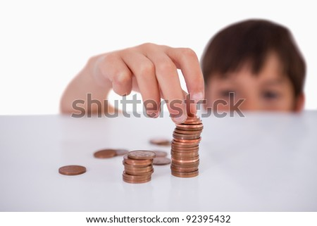 Little boy counting his change against a white background
