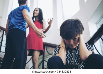 Little boy covering ears with hands during parents fighting quarrel , Stressed child Family violence concept