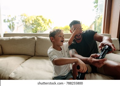 Little boy covering eyes of his father playing video game. Cheerful family of father and son having fun playing video games at home.