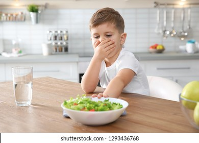 Little boy covering his mouth and refusing to eat vegetable salad at table in kitchen