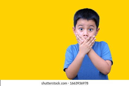 Little boy covering his mouth with his hands isolated on yellow background. Clipping path. Concept of surprised or scared.