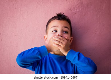 Little boy covering mouth with his hands looking at his left. Scared, stubborn or afraid of saying too much