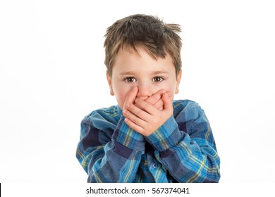 Little boy covering mouth with his hands looking straight ahead. Scared, stubborn or afraid of saying too much. Isolated on a white background.