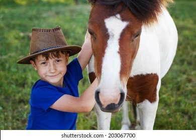 Little boy with cowboy hat and pony horse, friends