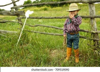 a little boy cowboy on nature