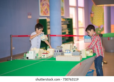 Little boy create build town and city by block many of buildings indoor activity