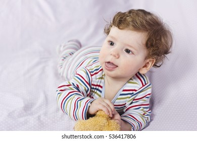 The little boy in the crib with toys. The child in the home