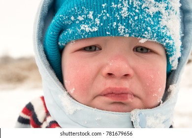 A little boy cries because he fell in the snow riding on sleds. Active rest on a winter day. Casual boy's fashion