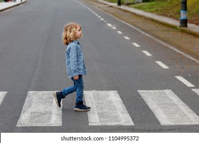 Little boy crossing alone on the road