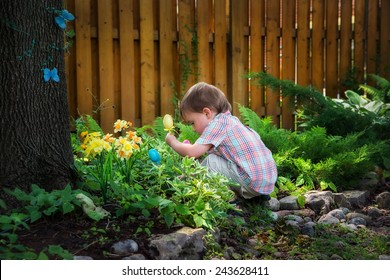 A little boy crouched down looking for Easter eggs in a garden on an Easter egg hunt during the spring season.