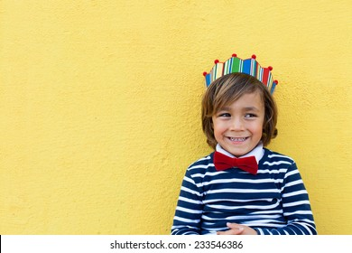 little boy with a crown, wearing a red bow tie and a stripes navy sweater.