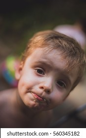 Little boy with crumbs on his face looking at camera.