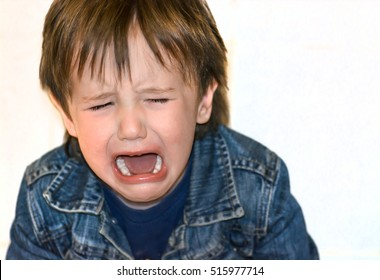Little boy is crying on a white background. Tantrum child