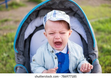 A little boy is crying in a stroller in a hat and jacket in the summer.