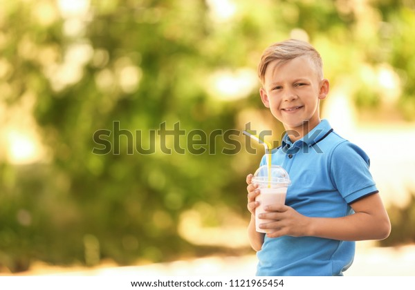 Little boy with cup of milk shake outdoors