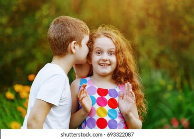 Little boy and curly redhead girl whispers in summer park.