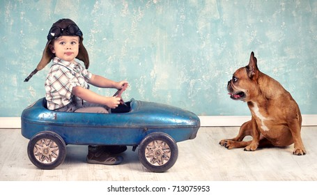 Little Boy and cute dog playing together, with pedal car