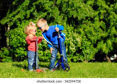 little boy and cute girl riding scooters in summer park