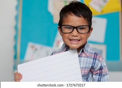 A little boy with a cute smile who is holding up a writting guide board and is wearing reading glasses with a preppy style shirt.