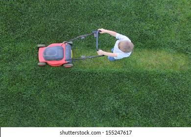 Little boy cuts a lawn using lawn-mower