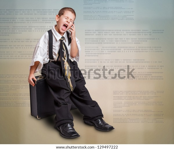 Little boy in daddy business suit sitting in briefcase