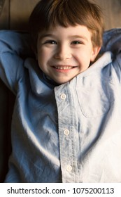 A little boy with dark hair and a blue shirt lies on the wooden floor and smiles