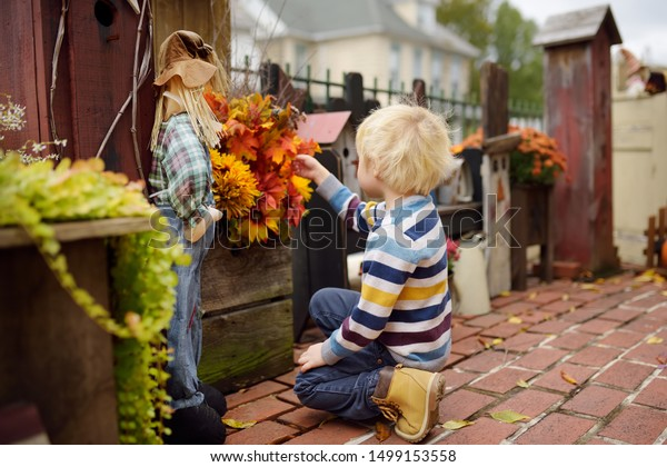 Little boy decorating by dried flowers and leafs porch and front door of his house for halloween on the street of New York.