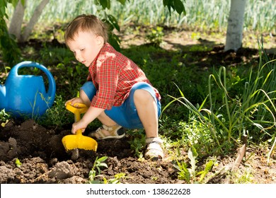 Little boy digging with a colourful yellow toy spade in fresh earth under the shade of a tree in the vegetable garden