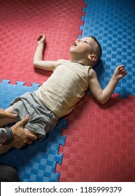 Little boy with disability has musculoskeletal therapy by doing exercises on floor mat