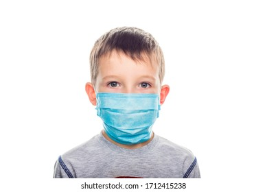 Little boy in a disposable mask on a light background. Kid is wearing the mask for protect them self from virus and air pollution.