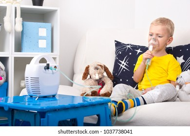 A little boy does inhalation with a nebulizer. A home treatment. A child and a toy dog in masks.