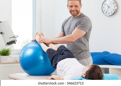 Little boy doing exercise with large ball