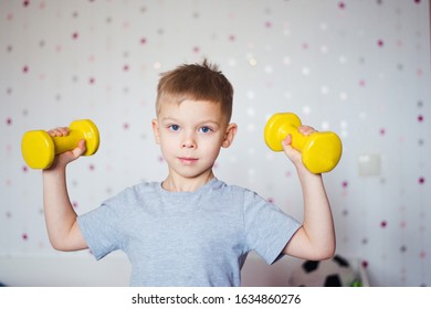 little boy doing exercises with dumbbells at home