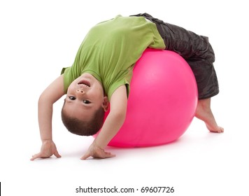 Little boy doing gymnastic exercises with a large rubber ball