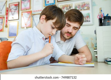Little boy doing home work in his room with tutor. Adult man helping child concept