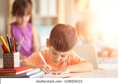 Little boy doing homework at table in classroom