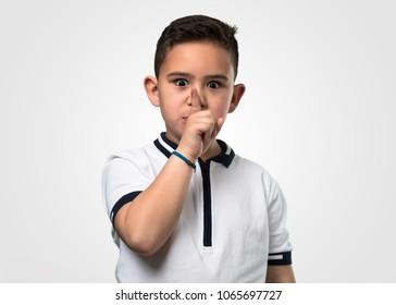 little boy doing silence gesture