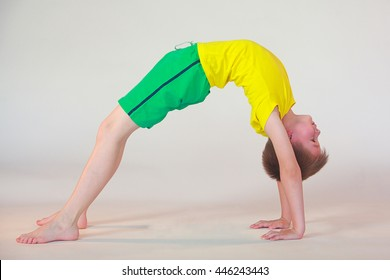 little boy doing yoga on white background