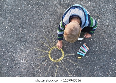 Little boy drawing with a chalk outdoors. Children's picture,creativity on gray dackground road,on asphalt sidewalk.Outside activities for children. top view, copy space.