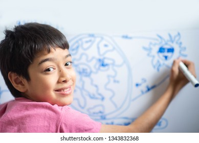 Little boy drawing eart on the whiteboard in the room