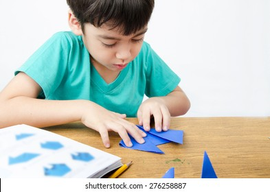Little boy drawing on paper art origami