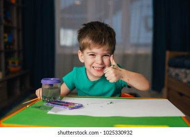 Little boy draws a brush and paint his first picture. Focus at the drawing