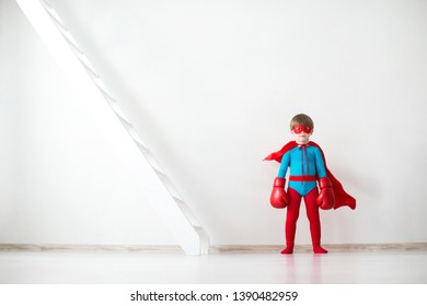 Little boy dreamer in a superhero costume and boxing gloves on the background of a wall with a ladder.